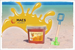 cubo de miel bonapi junto a una pala de juguete en la playa.